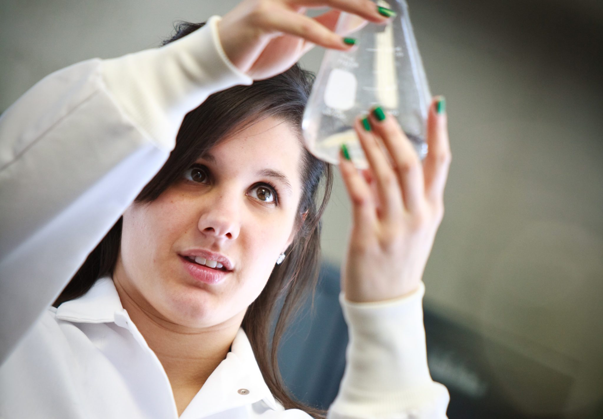 female student looks at glass bottle during science experiment
